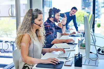 Buy stock photo Shot of a team of young people working in a call centre