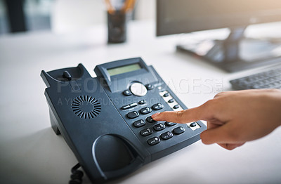 Buy stock photo Cropped shot of an unrecognizable businesswoman using the landline at work
