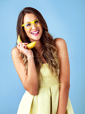 Buy stock photo Studio shot of an attractive young woman using a banana for a telephone against a blue background