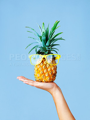 Buy stock photo Cropped shot of a woman holding a pineapple with glasses on against a blue background