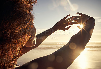 Buy stock photo Rearview shot of a young woman blocking the sunlight with her hands at the beach