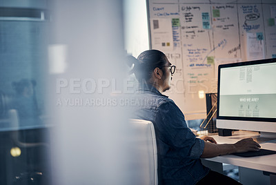 Buy stock photo Cropped shot of a handsome young creative businessman working on a computer in his office