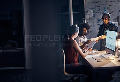 Buy stock photo Cropped shot of three young creative businesspeople meeting in their office at night
