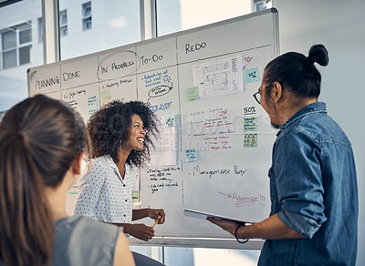 Buy stock photo Cropped shot of three young creative businesspeople working on a whiteboard during a meeting in their office at night