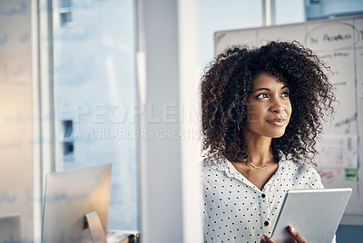 Buy stock photo Cropped shot of an attractive young creative businesswoman looking thoughtful while working on a tablet in her office