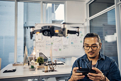 Buy stock photo Cropped shot of a handsome young creative businessman flying a drone in his office