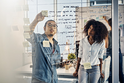 Buy stock photo Cropped shot of two young creative businesspeople working on a glass wipe board in their office