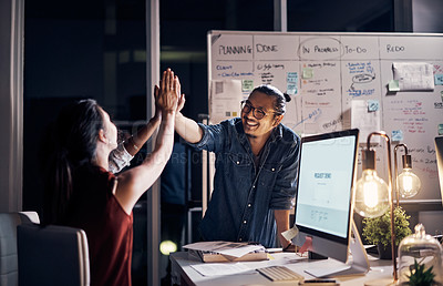 Buy stock photo Cropped shot of two young creative businesspeople high fiving during a meeting in their office at night
