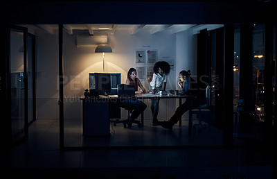 Buy stock photo Full length shot of three young creative businesspeople meeting in their office at night