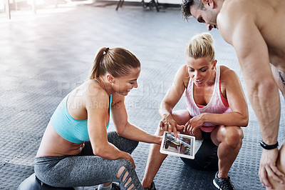 Buy stock photo Shot of a group of people using a digital tablet at the gym