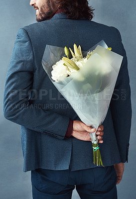Buy stock photo Studio shot of a stylishly dressed young man holding a bouquet of flowers behind his back against a gray background