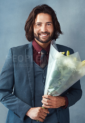 Buy stock photo Studio shot of a stylishly dressed handsome young man holding a bouquet of flowers against a gray background