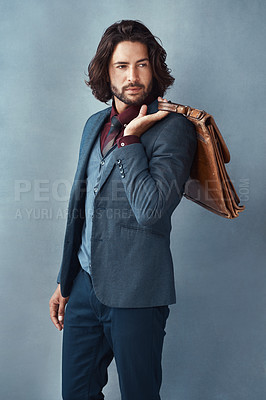 Buy stock photo Studio shot of a handsome and dapper young man carrying a bag against a grey background