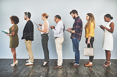 Buy stock photo Shot of a group of business people using their smart devices while waiting in line