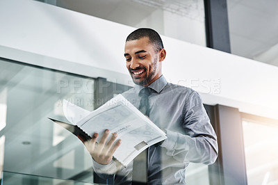 Buy stock photo Shot of a young businessman going over paperwork in a modern office