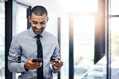Buy stock photo Shot of a young businessman using a smartphone and credit card in a modern office