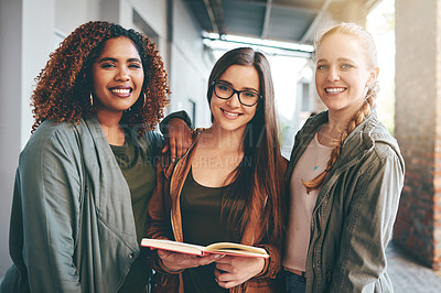 Buy stock photo Portrait of a group of young students reading a notebook together on campus