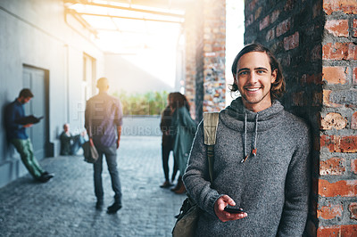 Buy stock photo Shot of a young man using a mobile phone outdoors on campus