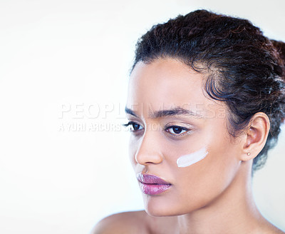Buy stock photo Studio shot of a beautiful young woman with moisturiser on her face
