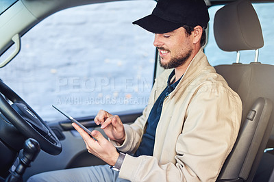 Buy stock photo Shot of a courier writing on a clipboard while sitting in a delivery van