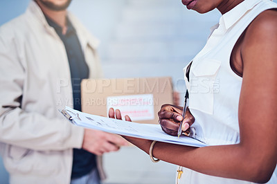Buy stock photo Closeup shot of a businesswoman signing for her delivery from the courier