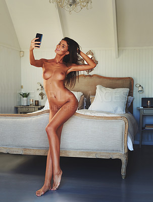 Buy stock photo Full length shot of a gorgeous young woman taking a selfie while nude in her bedroom at home