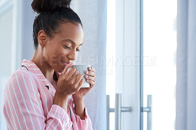 Buy stock photo Shot of an attractive young woman enjoying her morning coffee at home