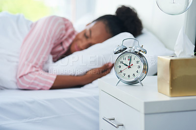 Buy stock photo Shot of an attractive young woman sleeping in bed with her alarm clock on the dresser at home