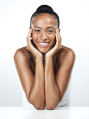 Buy stock photo Studio portrait of an attractive young woman resting her face in the palm of her hands while standing against a white background
