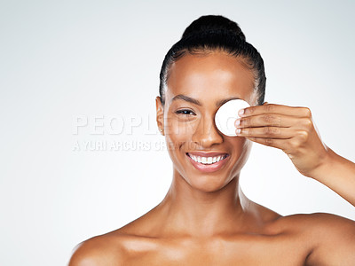 Buy stock photo Studio portrait of an attractive young woman holding a cotton pad in front of her one eye while standing against a grey background