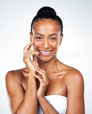 Buy stock photo Studio portrait of an attractive young woman posing and gently touching her neck while standing against a white background