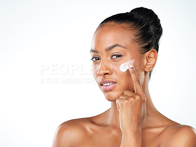Buy stock photo Studio portrait of an beautiful young woman applying skin moisturizer to her face while standing next to a white background