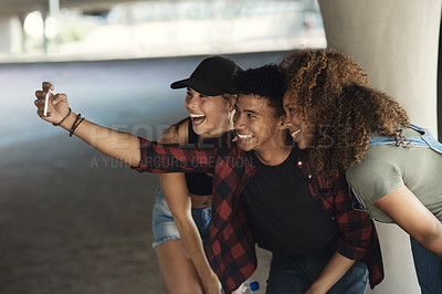 Buy stock photo Shot of a group of cheerful young friends posing for a self portrait together while outside in a parking lot