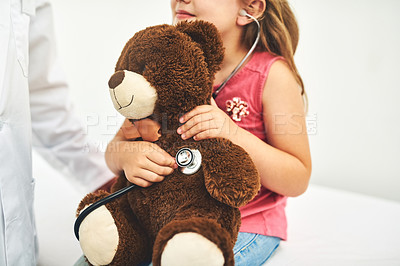 Buy stock photo Shot of an adorable little girl examining her teddybear with a stethoscope during a checkup