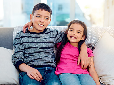 Buy stock photo Portrait of two adorable young siblings posing with their arms around each other while relaxing on a sofa at home