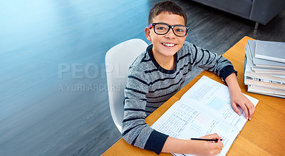 Buy stock photo Portrait of a determined young boy doing his homework at home