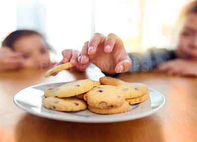 Buy stock photo Closeup shot of two mischievous young children stealing cookies on the kitchen table at home