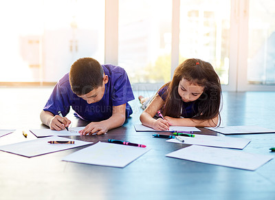 Buy stock photo Shot of two young children lying down on the floor and coloring in pictures in their coloring books at home