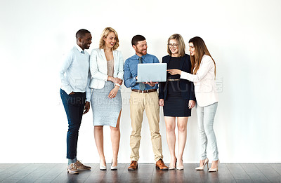 Buy stock photo Shot of a group of work colleagues standing in a line while using their wireless devices against a white background