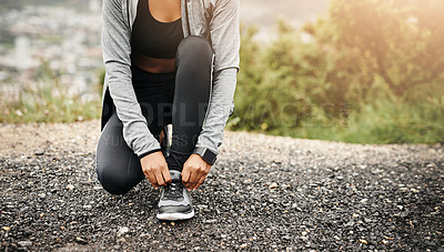 Buy stock photo Closeup shot of a sporty woman tying her shoelaces while exercising outdoors
