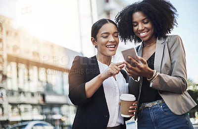 Buy stock photo Shot of two businesswomen looking at something on a cellphone in the city