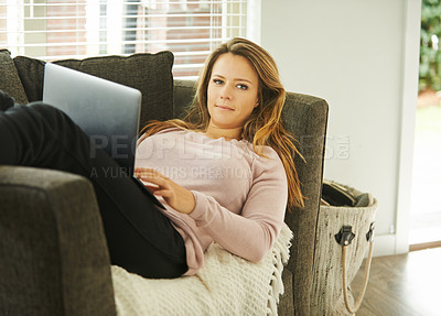 Buy stock photo Shot of a young woman using a laptop while relaxing on the sofa at home