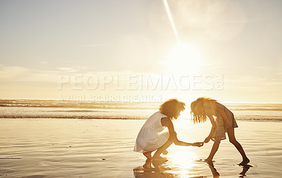 Buy stock photo Shot of a mother and her little daughter picking up seashells at the beach