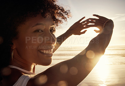 Buy stock photo Portrait of a young woman blocking the sunlight with her hands at the beach