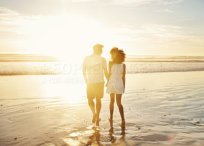 Buy stock photo Rearview shot  of a young couple bonding at the beach