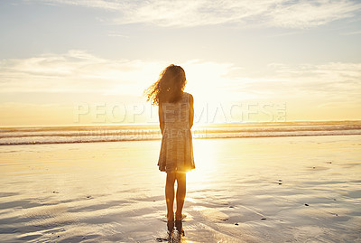 Buy stock photo Rearview shot of a young girl standing on the beach