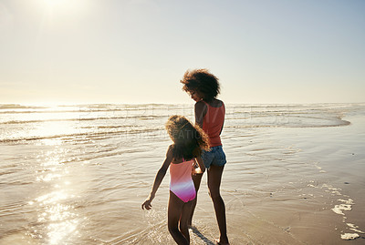 Buy stock photo Rearview shot  of a mother and her little daughter bonding together at the beach