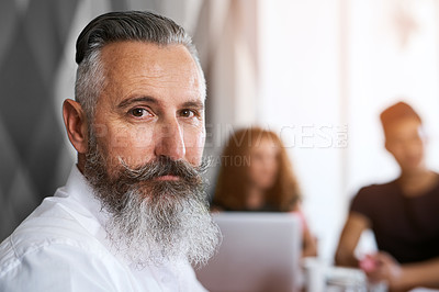 Buy stock photo Portrait of a mature businessman sitting in an office with his colleagues in the background