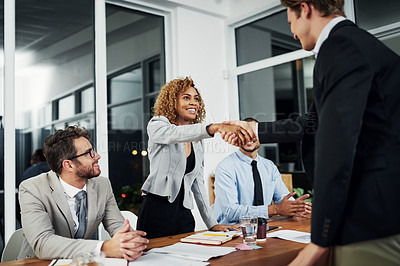 Buy stock photo Cropped shot of two businesspeople shaking hands during a job interview in an office