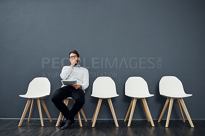 Buy stock photo Cropped shot of a handsome young man yawning while waiting in line for a job interview